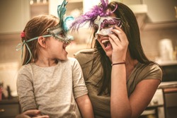 Mother and daughter have play with carnival mask.