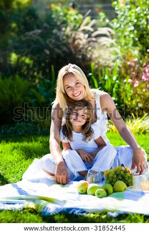 Mother and daughter having a picnic in  a park