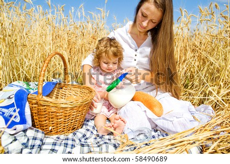 Mother and daughter having breakfast in field