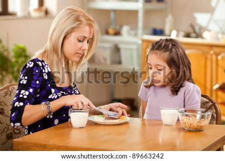 mother and daughter having breakfast: spreading chocolate cream on a slice of bread