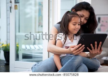 Mother and Daughter having fun on a digital tablet in a home interior