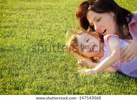 Mother and daughter having fun on grass