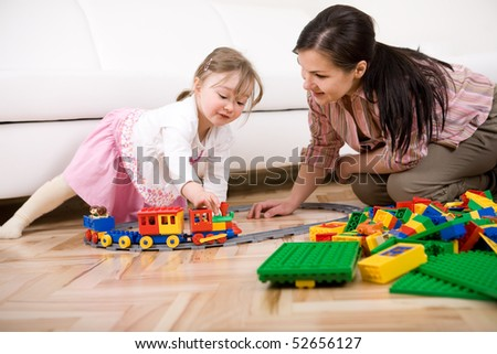 mother and daughter having fun with bricks at home
