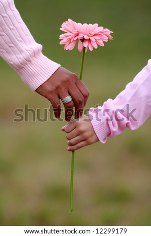 Mother and daughter holding a flower while walking together - stock photo
