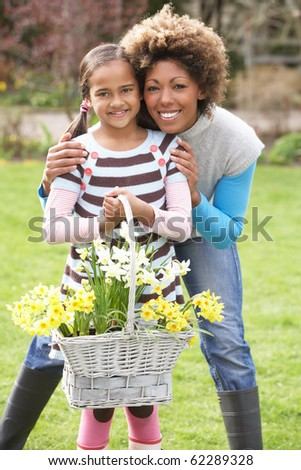 Mother And Daughter Holding Basket Of Daffodils In Garden