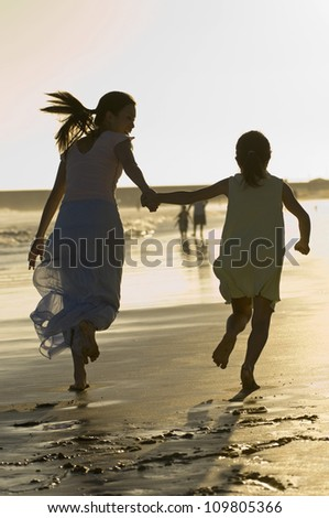 Mother and daughter holding hands and running on the beach