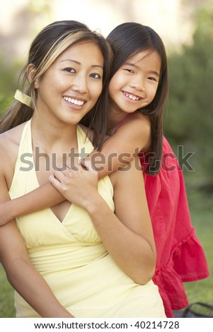 Mother And Daughter Hugging In Garden