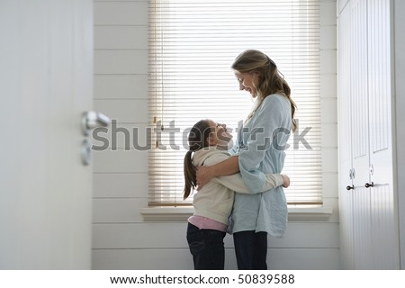Mother and daughter hugging, standing in front of  window