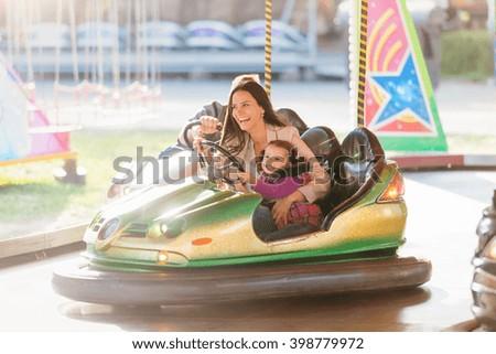 Mother and daughter in bumper car at fun fair