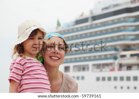 mother and daughter in dock, big cruise ship on background