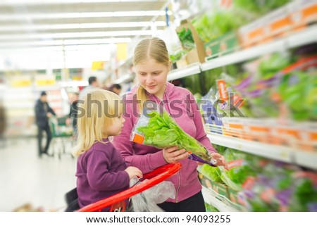 mother and daughter in fruit and vegetables section in supermarket