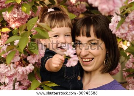 Mother and daughter in garden, under the sakura tree. Spring.