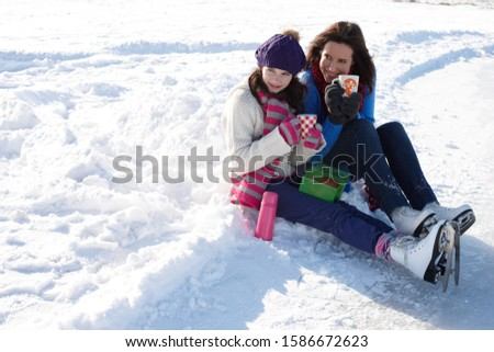 Mother and daughter in ice skates sitting together and drinking hot chocolate on winter day