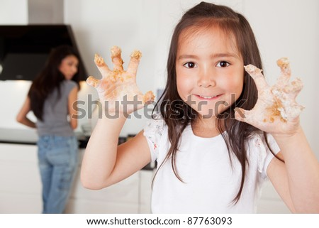 Mother and daughter in kitchen, child looking at camera with cookie dough on hands