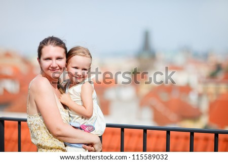 Mother and daughter in Prague enjoying red roofs view