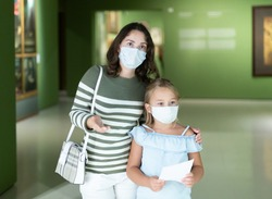 Mother and daughter in protective masks with guide enjoying expositions in museum