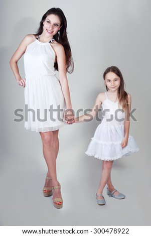 mother and daughter in same outfits posing on studio kissing #300478922