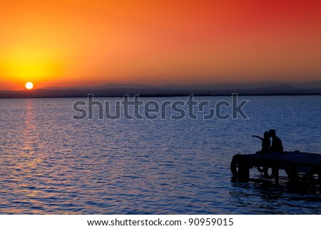 Mother and daughter in sunset jetty lake with orange sun - stock photo