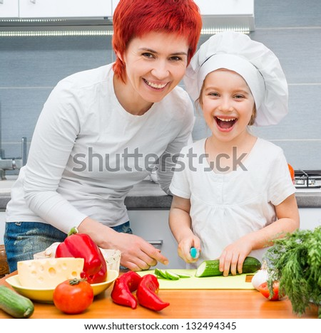 Mother and daughter in the kitchen cutting cucumber