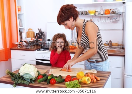 Mother and daughter in the kitchen preparing a salad - stock photo