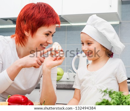Mother and daughter in the kitchen with mushrooms