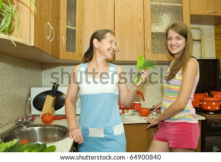 mother and daughter in the kitchen with some vegetables