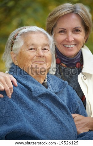 Mother and daughter in the park. Focus on the senior woman. - stock photo