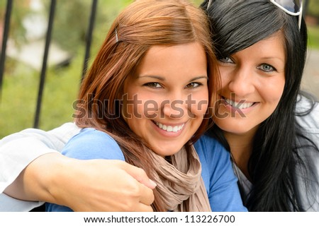 Mother and daughter in the park smiling teen together loving