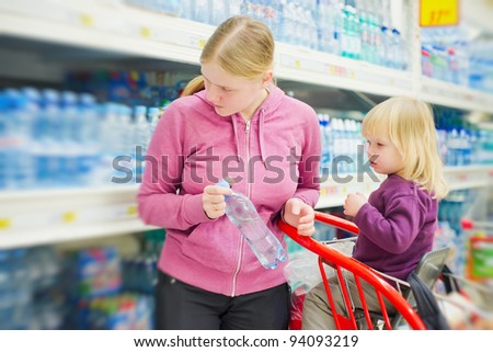 mother and daughter in water section in supermarket
