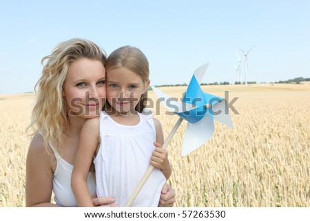 Mother and daughter in wind turbines field