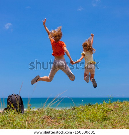 mother and  daughter jumping at the beach in the day time