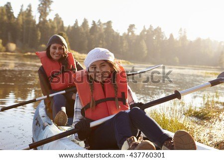 Mother and daughter kayaking on rural lake, close up