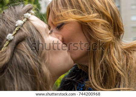 Mother and daughter kiss affectionately on cheek in a special and affectionate way #744200968
