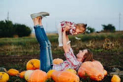 mother and daughter lie between pumpkins on the field, Halloween eve