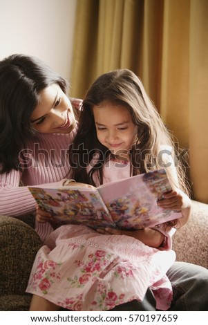 mother and daughter look at story book