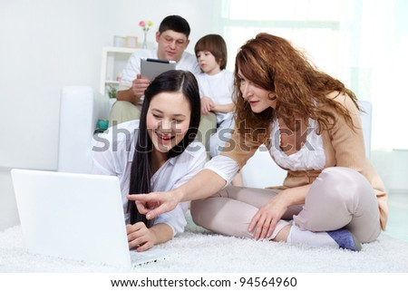 Mother and daughter looking at laptop screen with father and son at background