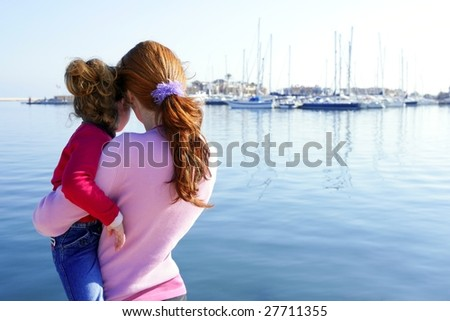 Mother and daughter looking blue marina on the sea