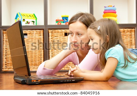 mother and daughter looking the laptop