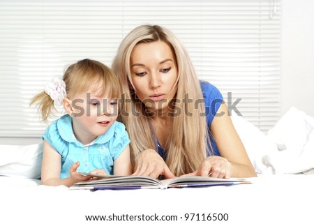 Mother and daughter lying on a light background - stock photo