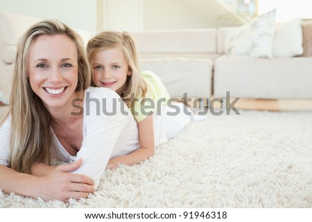 Mother and daughter lying on the floor together