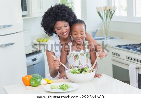 Mother and daughter making a salad together at home in the kitchen