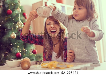 Mother and daughter making Christmas cookies and having fun. Mother sifts the flour through a sieve while daughter puts more flour in it. Focus on the mother