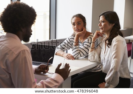Mother And Daughter Meeting With Male Teacher