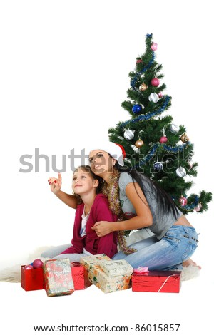 Mother and daughter near a christmas tree with gifts, isolated on a white background
