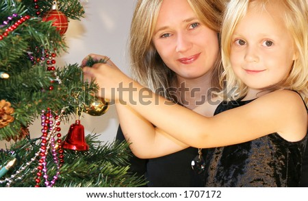 Mother and daughter next to christmas tree