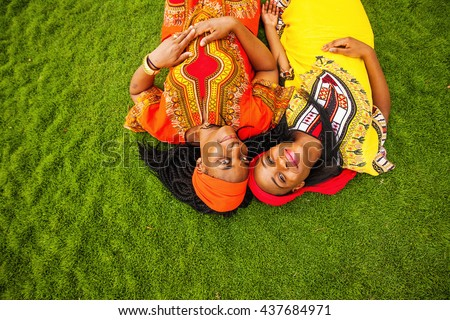 mother and daughter of African ethnicity lying down on a grass