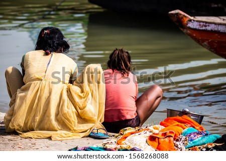 Mother and daughter of low caste washing their clothes in the Ganges river, in Varanasi, India.