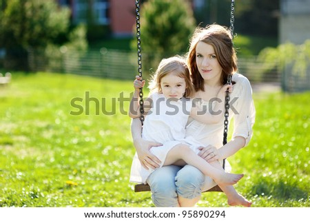 Mother and daughter on a garden swing