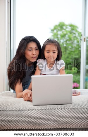 Mother and daughter on couch using laptop