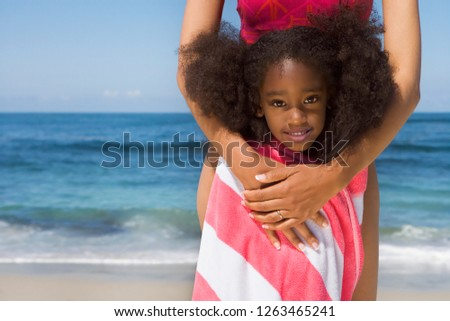 Mother and daughter on sandy beach wrapped in striped towel at camera